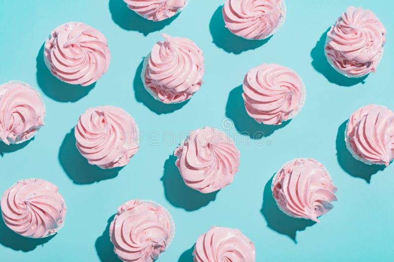 Rosa muffin på blå bakgrund royaltyfri fotografi