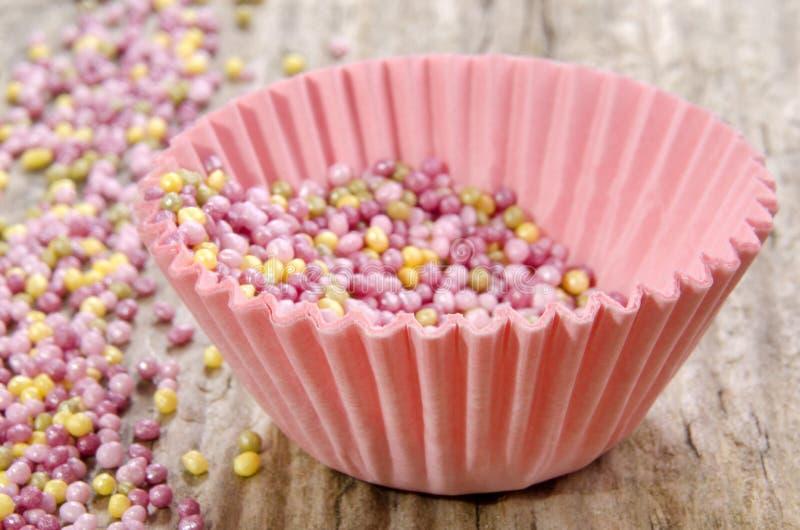 Rosa muffinfall med sockerstänk arkivbilder