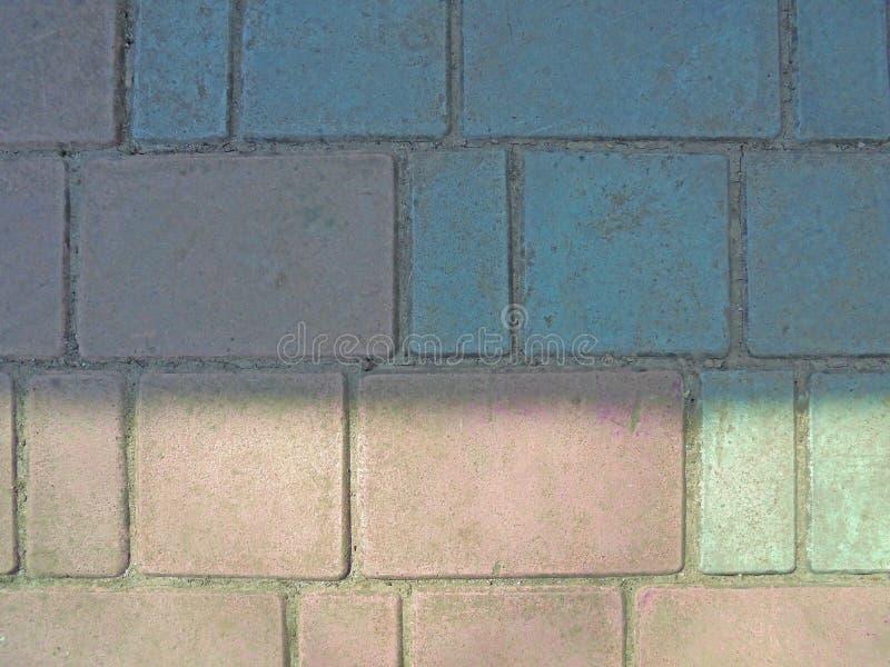 Rosa och blå grå trottoartegelplattahalva exponerad av solen royaltyfria bilder