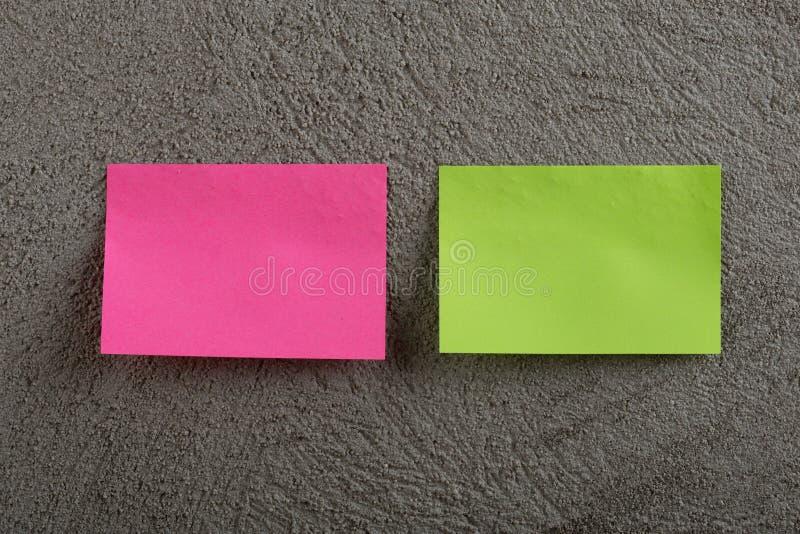Rosa och grön klibbig anmärkning på grå konkret bakgrund kopiera avst?nd royaltyfria bilder