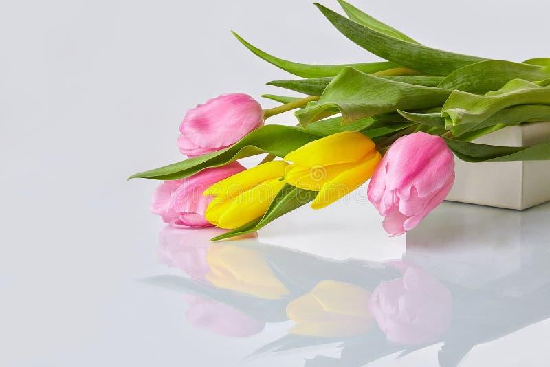 Rosa och gul tulpanbukett som lägger på en tabell royaltyfri foto