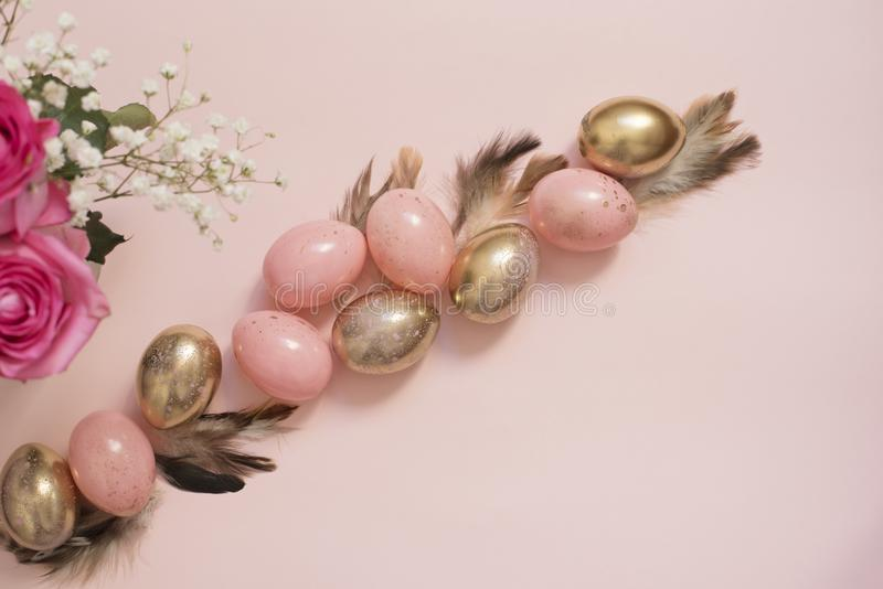 Rosa och guld- påskägg Pastellfärgat påskbegrepp med ägg, blommor och fjädrar Punchy pastell royaltyfri fotografi