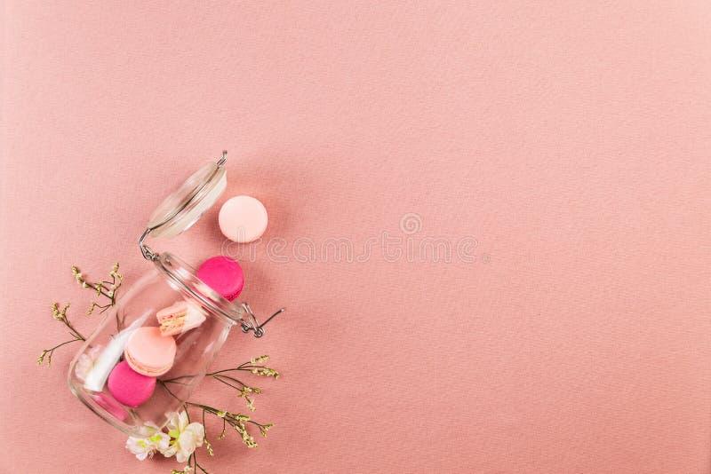 Rosa och magentafärgade franska macarons eller makron som faller ut ur en exponeringsglaskrus med vita blommor över en rosa bakgr arkivbild