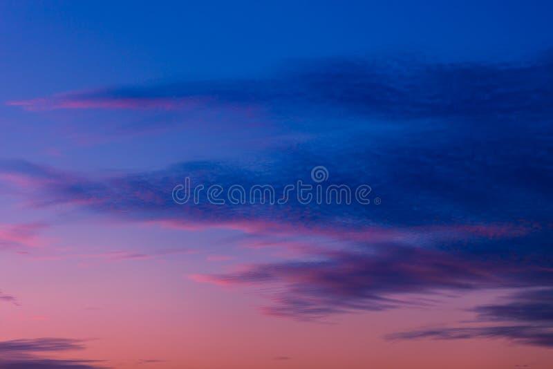 Rosa och purpurfärgad solnedgånghimmel med moln som målas i mörka signaler av blått arkivbilder