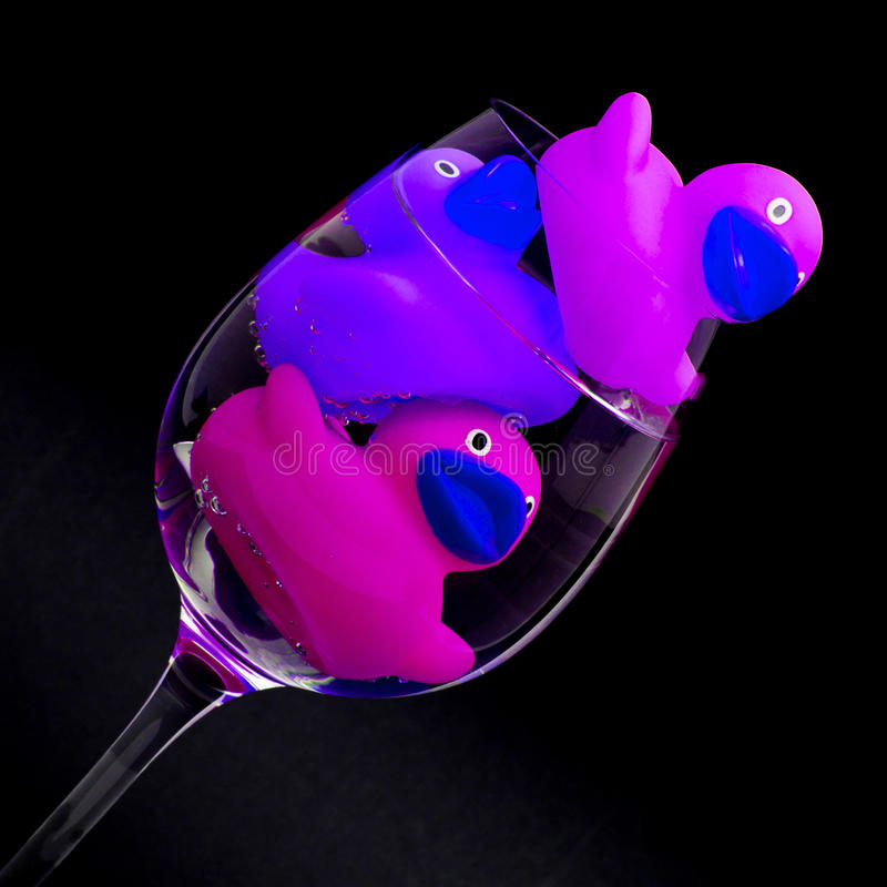 Rosa och purpurfärgade rubber änder i vinglas arkivbilder