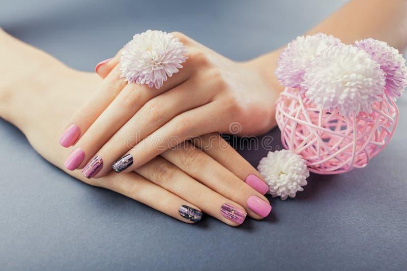 Rosa och svart manikyr på kvinnliga händer med blommor på grå bakgrund Spika konst och designen royaltyfria foton
