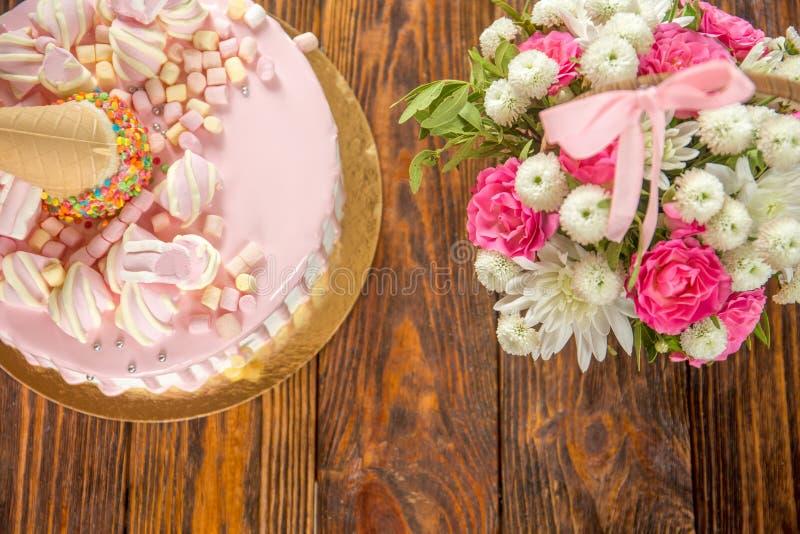 Rosa och vit kaka med marshmallowen på det celebratory födelsedagpartiet av lilla flickan royaltyfri bild