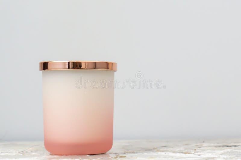 Rosa rosa och vit ombrestearinljuskrus med det skinande guld- locket som sitter på en nattduksbordnattställning Stearinljuset t fotografering för bildbyråer