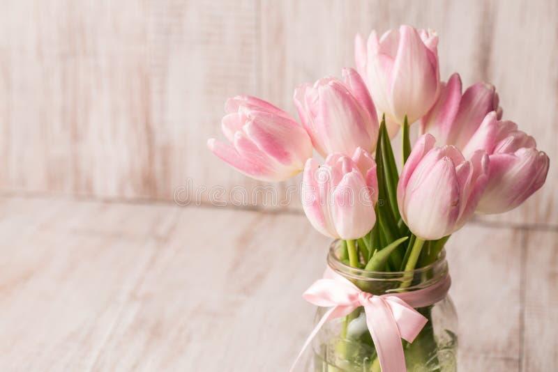 Rosa och vita pastellfärgade tulpan i den Glass krusvasen med rum för Tex royaltyfri foto
