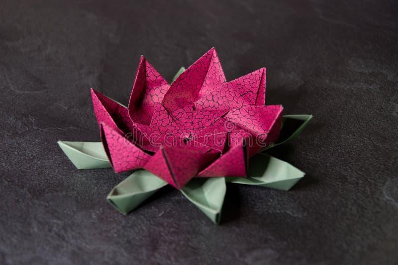 Rosa origami Lotus Flower - pappers- konst p? texturerad bakgrund royaltyfri bild