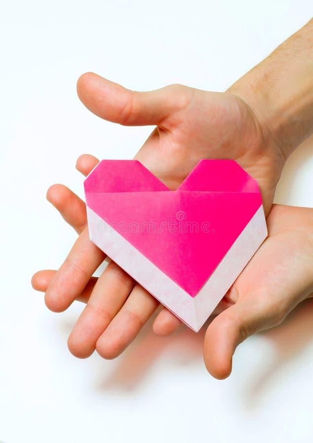 Rosa origamihjärta i händer för man` s arkivfoto