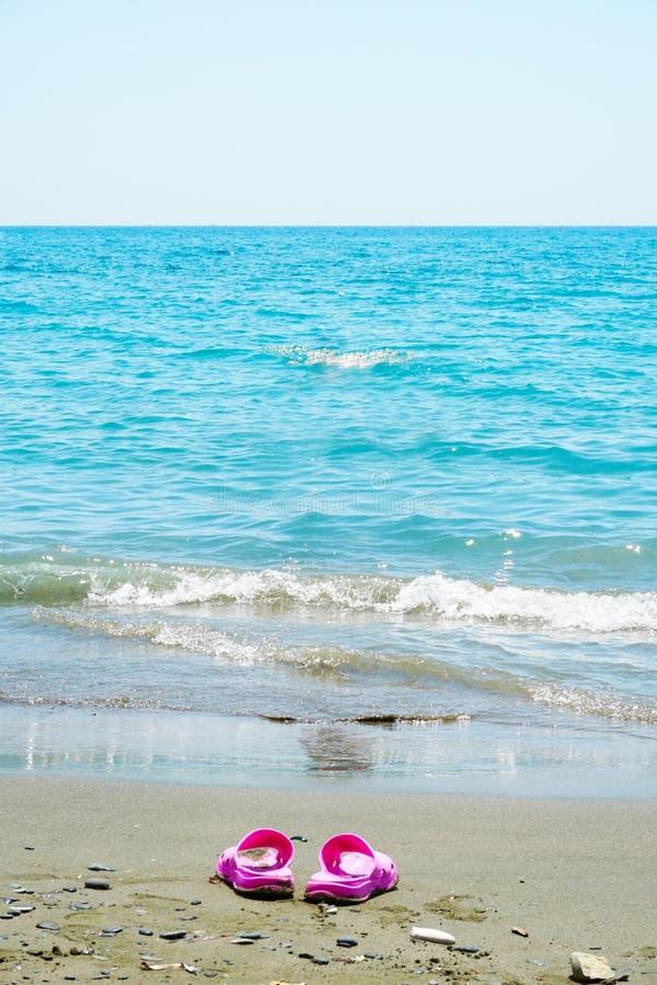 Rosa Pantoffel auf einem sandigen Strand von schönem blauem Meer an einem heißen sonnigen Tag lizenzfreie stockfotografie