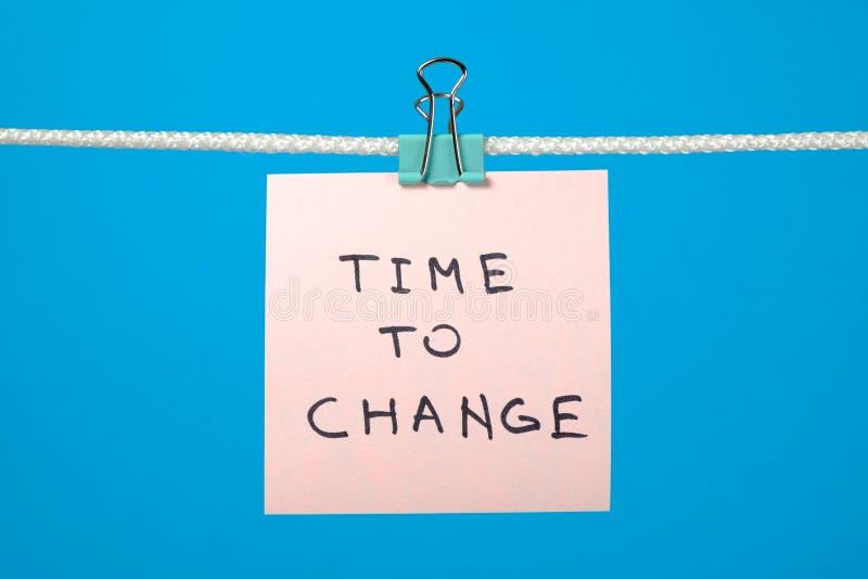 Rosa Papieranmerkung, die an der Schnur mit Text Zeit zu ändern hängt stockbild