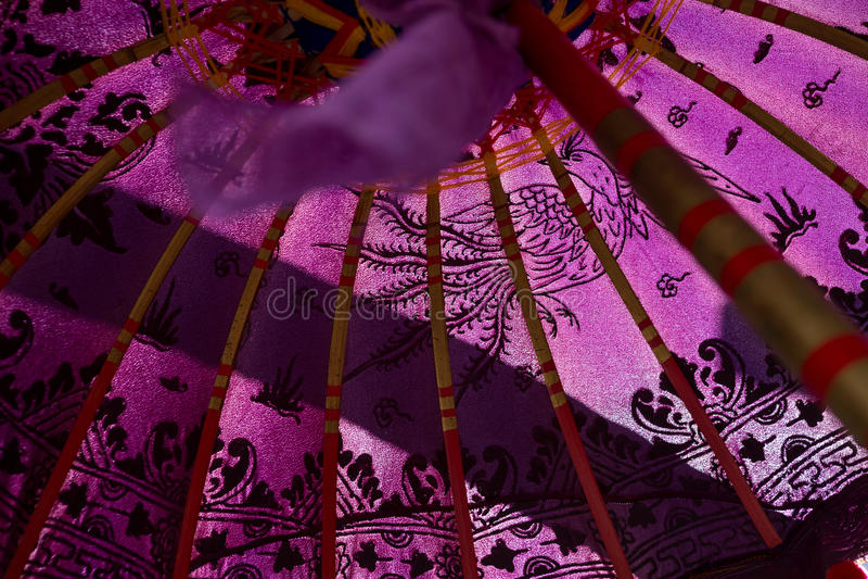Rosa Papierregenschirm mit Krandesign lizenzfreie stockbilder