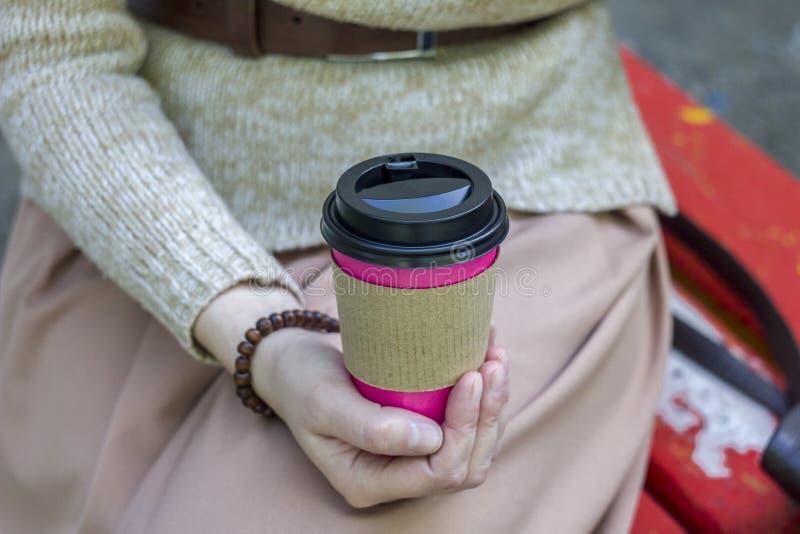 Rosa Papiertasse kaffee in den Händen eines Mädchens auf einem unscharfen Hintergrund stockbilder