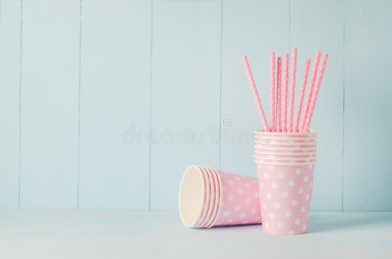 Rosa pappers- kopp och sugrör på blå bakgrund royaltyfri foto