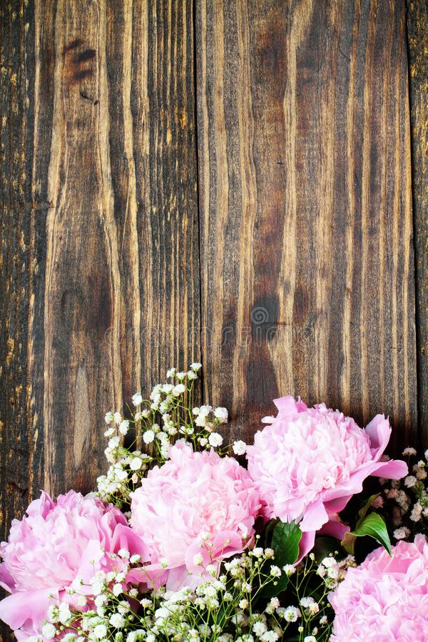 Rosa Peonies und Babys Atemblumen über einem natürlichen rustikalen Holzgrund lizenzfreie stockfotos