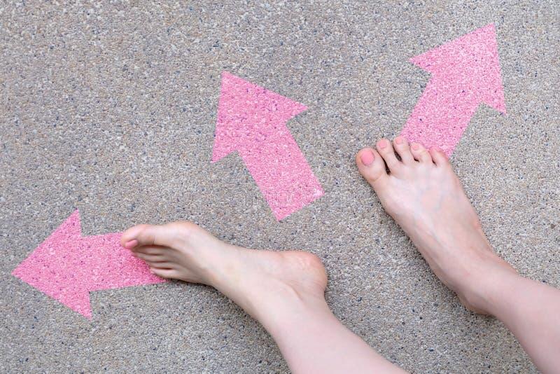 Rosa Pfeil-Wahl-Konzept Weibliche bloße Füße mit rosa Nagellack-Maniküre-Stellung und viele Richtungs-Pfeil-Wahlen auf der Straße stockfotografie