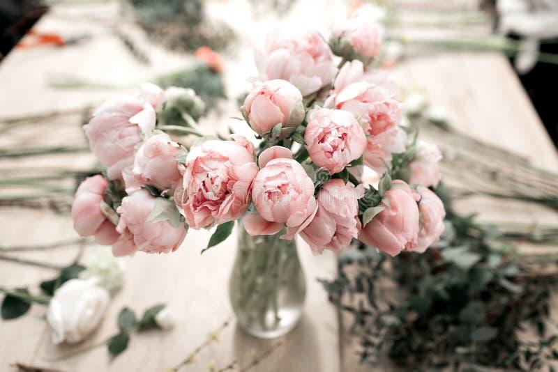 Rosa Pfingstrosen im Vase auf Bretterboden und bokeh Hintergrund - Retro- angeredetes Foto Weicher Fokus stockfoto