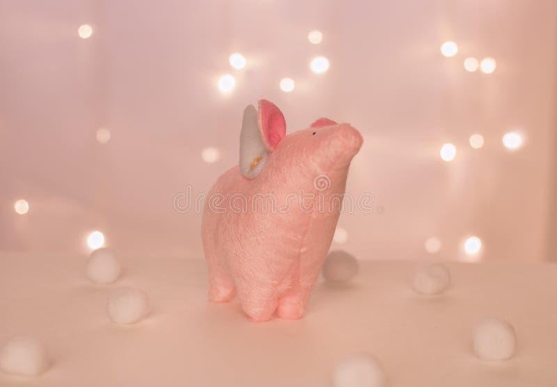 Rosa piggy ängel med handgjorda vingställningar på bakgrunden av julljus och mjuka bollar arkivbild