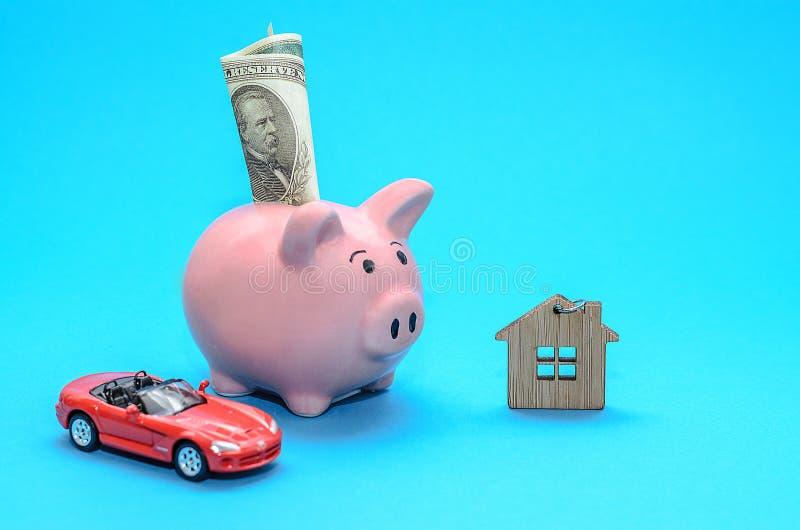 Rosa piggy spargris med ett hus och en bil på tabellen tonat Begrepp av sparande finanser och fastighetinsättningar royaltyfri bild