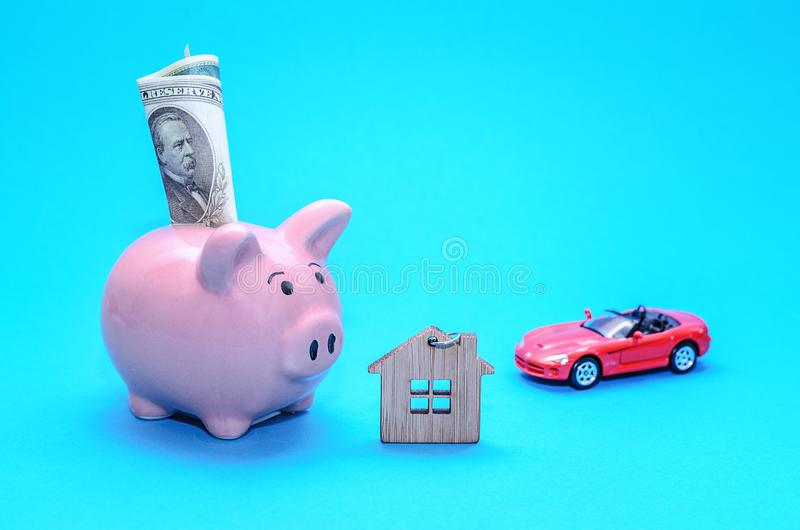 Rosa piggy spargris med ett hus och en bil på tabellen tonat Begrepp av sparande finanser och fastighetinsättningar fotografering för bildbyråer