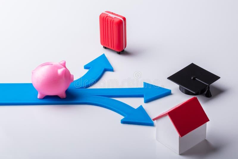 Rosa Piggybank auf den blauen Pfeilen, die verschiedene Wahlen zeigen lizenzfreie stockfotos