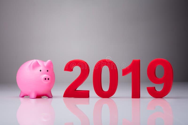 Rosa Piggybank förutom året 2019 royaltyfria foton