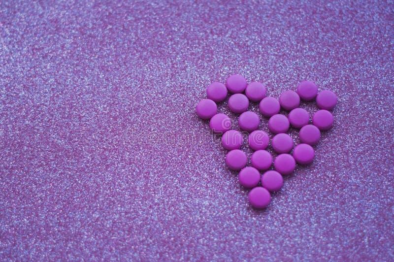 Rosa piller lade ut i form av en hjärta blänker på rosa bakgrund arkivfoton