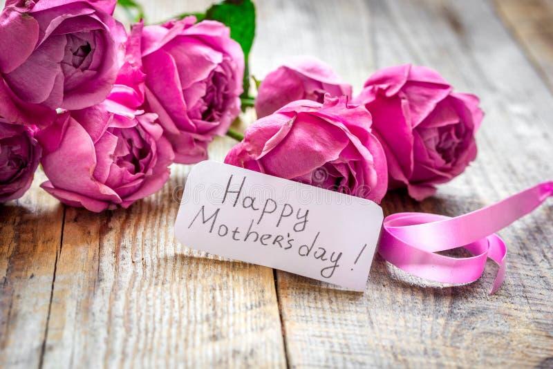 Rosa pion och hälsning-kort för den närvarande dagen för moder` s på träbakgrund arkivbilder
