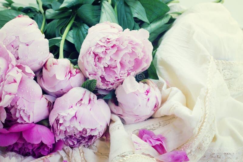 Rosa pioner och vit bröllopsklänning royaltyfria bilder