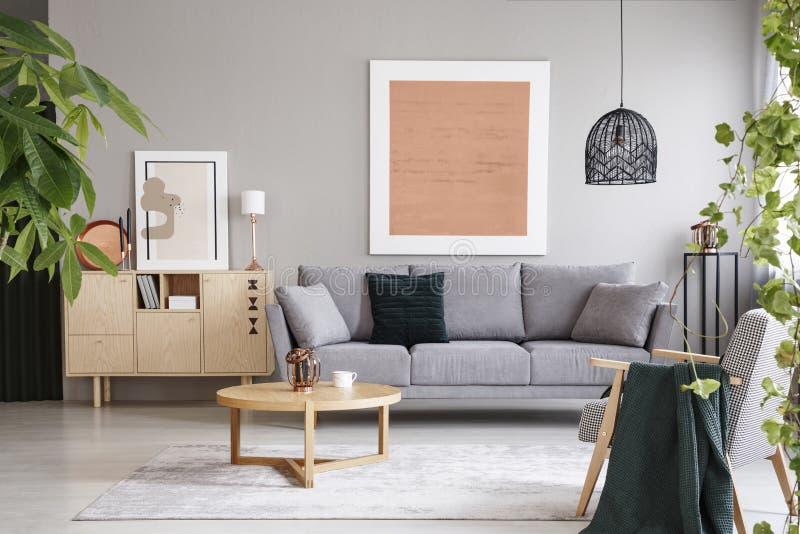 Rosa Plakat über grauem Sofa im Wohnzimmerinnenraum mit Holztisch nahe Schrank Reales Foto lizenzfreie stockfotografie