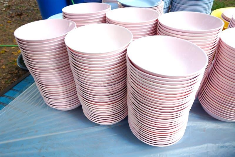 Rosa plast-bunkar på hyllor royaltyfria foton