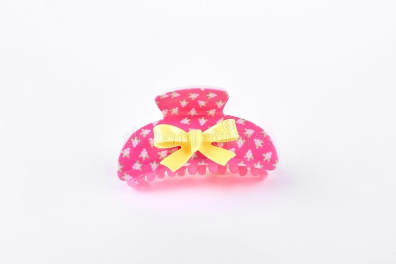 Rosa plast- hårnål med den gula pilbågen royaltyfri foto