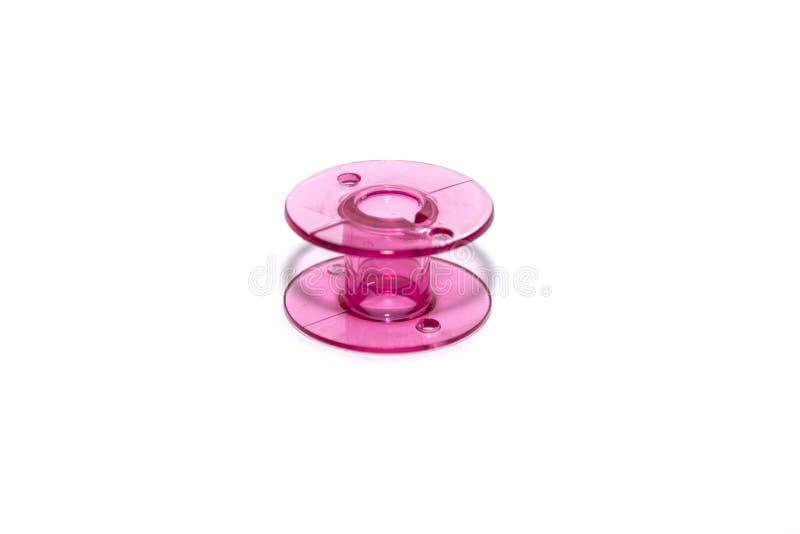 Rosa plast- spole för symaskin arkivbilder