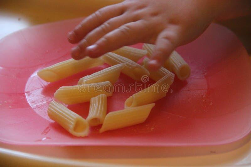 Rosa Plastikplatte und Penne-Teigwaren Kleines Baby isst penne Teigwarengluten frei lizenzfreies stockfoto