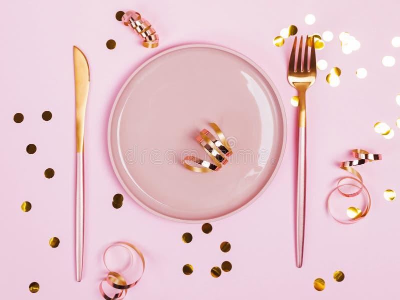 Rosa platta, gaffel och kniv och guld- connfetti och band på rosa bakgrund, royaltyfri foto