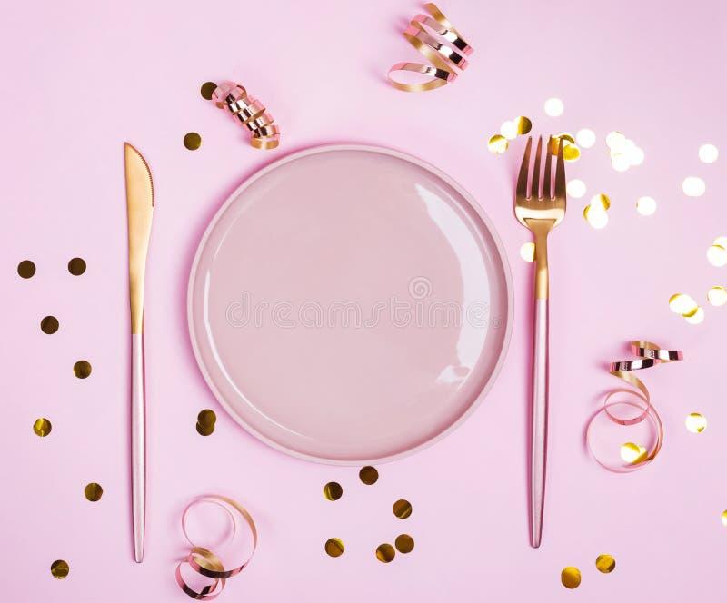Rosa platta, gaffel och kniv och guld- connfetti och band på rosa bakgrund, royaltyfria bilder