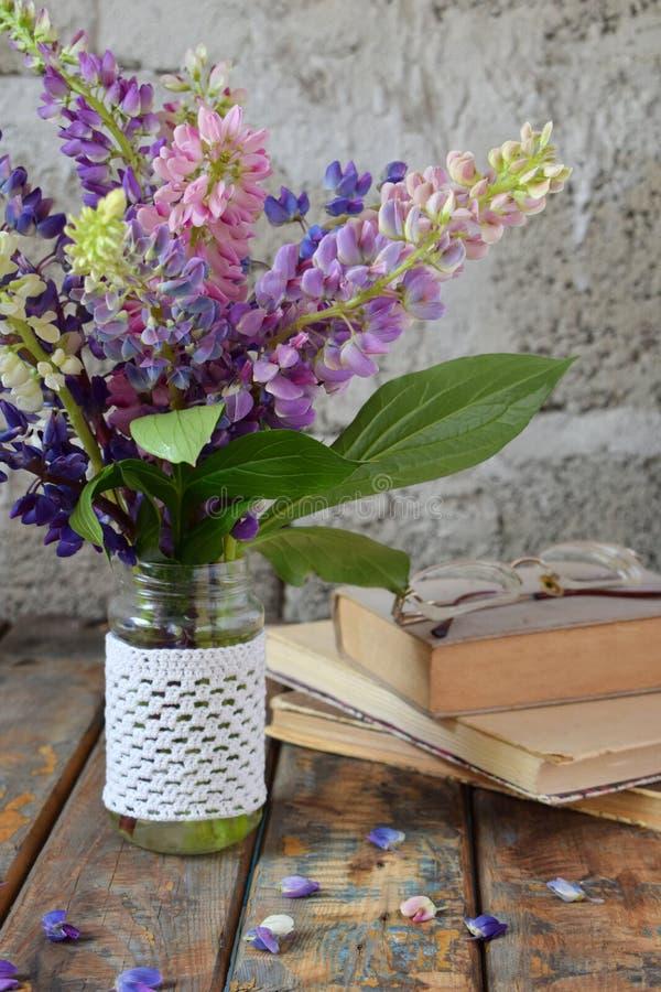Rosa, purpurroter lupine Blumenblumenstrauß im Vase und altes Buch Geburtstag, Muttertag, Valentinstag, am 8. März, Hochzeitskart stockbild
