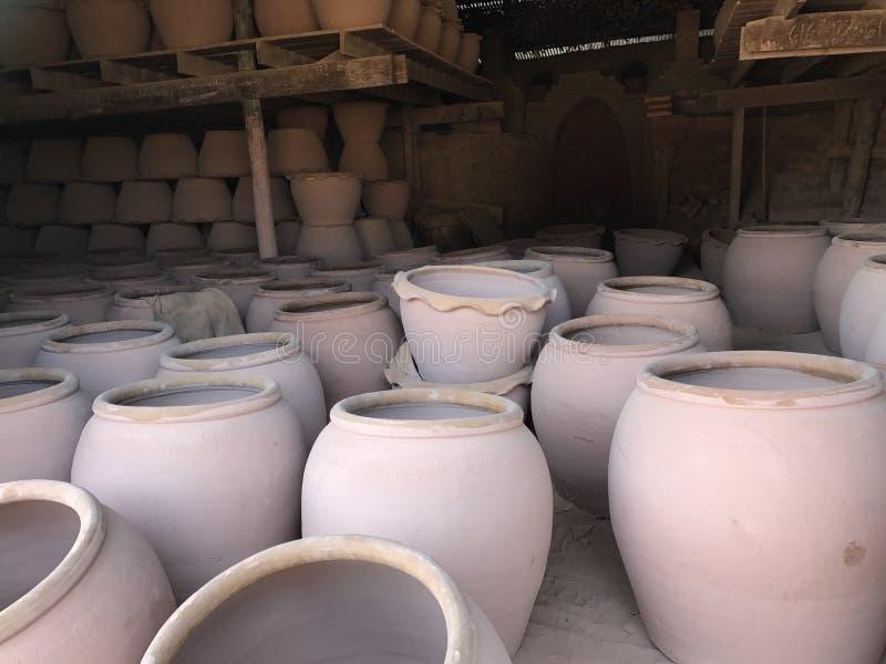 Rosa rå krukmakeri som är klar att laddas in i brännugnen nästa gång Vänta som torkar nog för att bränna i brännugn royaltyfri bild