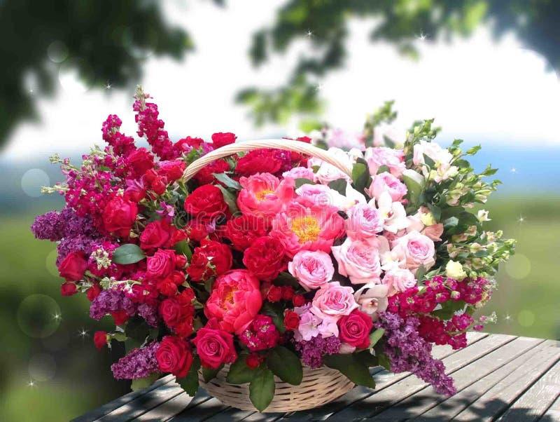 Rosa röda rosor i en korg på en bakgrund av ett landskap, på en trätabell stock illustrationer