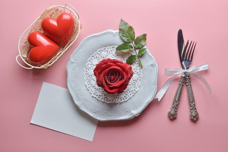Rosa roja en el plato blanco, con la bifurcación y el cuchillo, en fondo rosado, concepto del día de tarjeta del día de San Valen imagenes de archivo