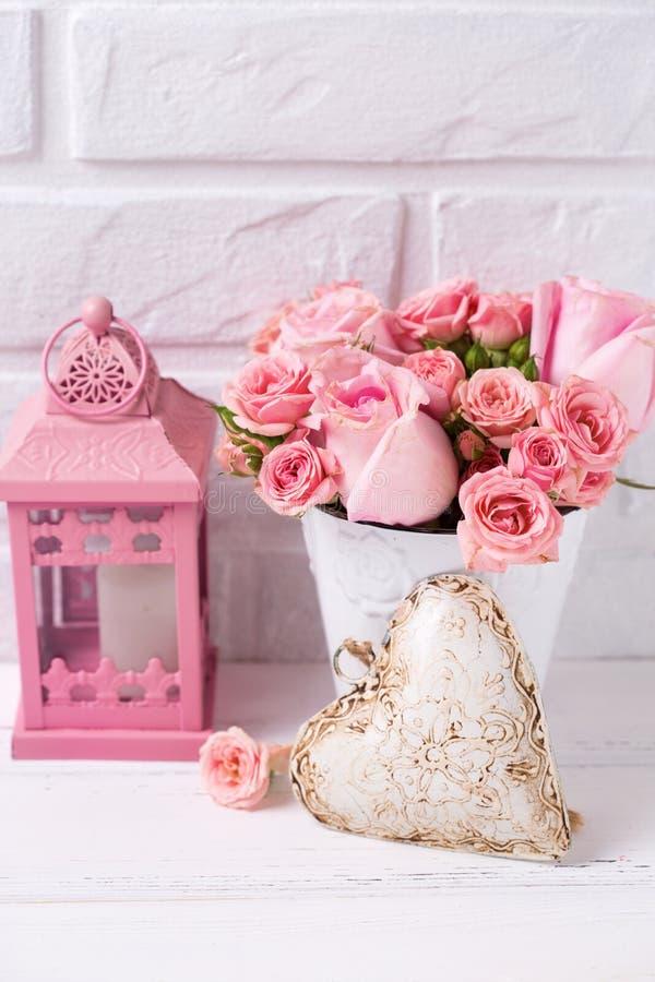 Rosa rosblommor i den vita lant krukan, dekorativ hjärta och rosa färger arkivfoto