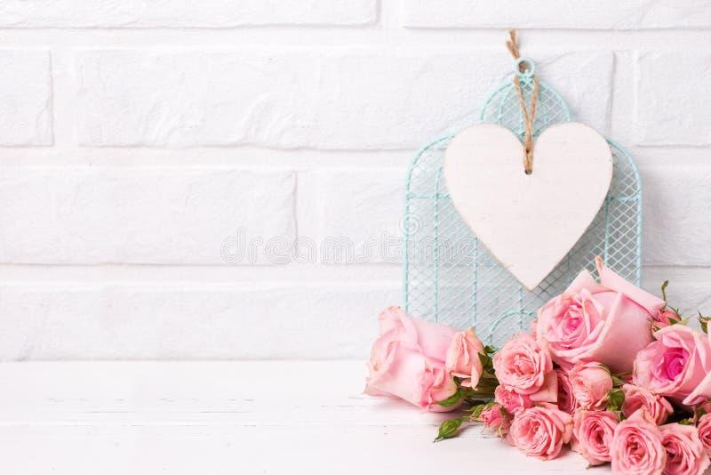 Rosa rosblommor och, dekorativ fågelbur och vithjärta ag royaltyfria foton