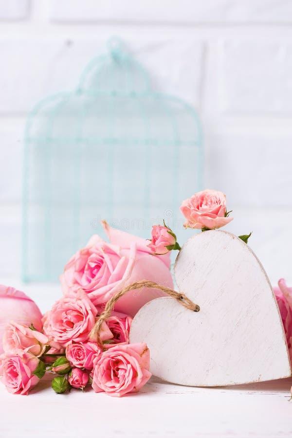 Rosa rosblommor och dekorativ vit hjärta mot vit b royaltyfri bild