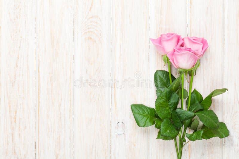 Rosa rosbukett över trätabellen royaltyfria foton