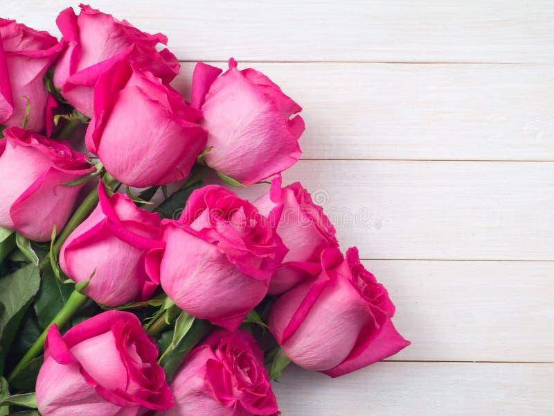 Rosa rosbukett på de vita plankorna royaltyfri bild