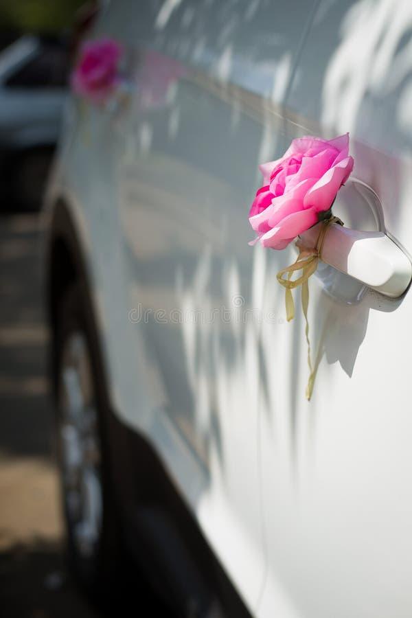 Rosa Rosen auf der Autot?r Hochzeitsautodekorationen Hochzeitszug stockfotos