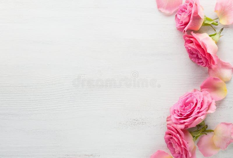 Rosa Rosen auf einem schäbigen Holztisch Flache Lage lizenzfreies stockbild