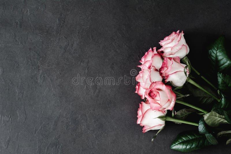 Rosa Rosen auf Steinhintergrund, angeredeter Blumenhintergrund stockfoto